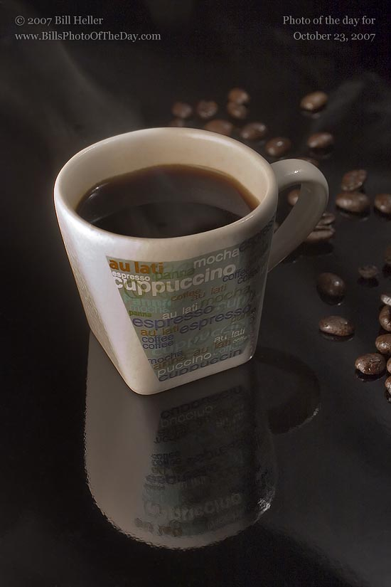 Cup of Espresso and Espresso Beans on a shiny black surface